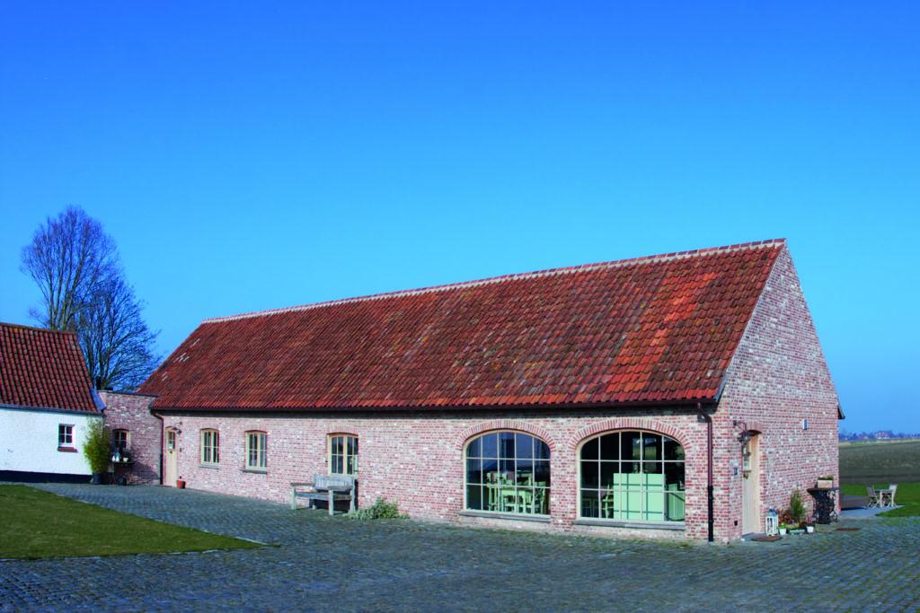 Luxury converted barn against a blue sky in De Haan