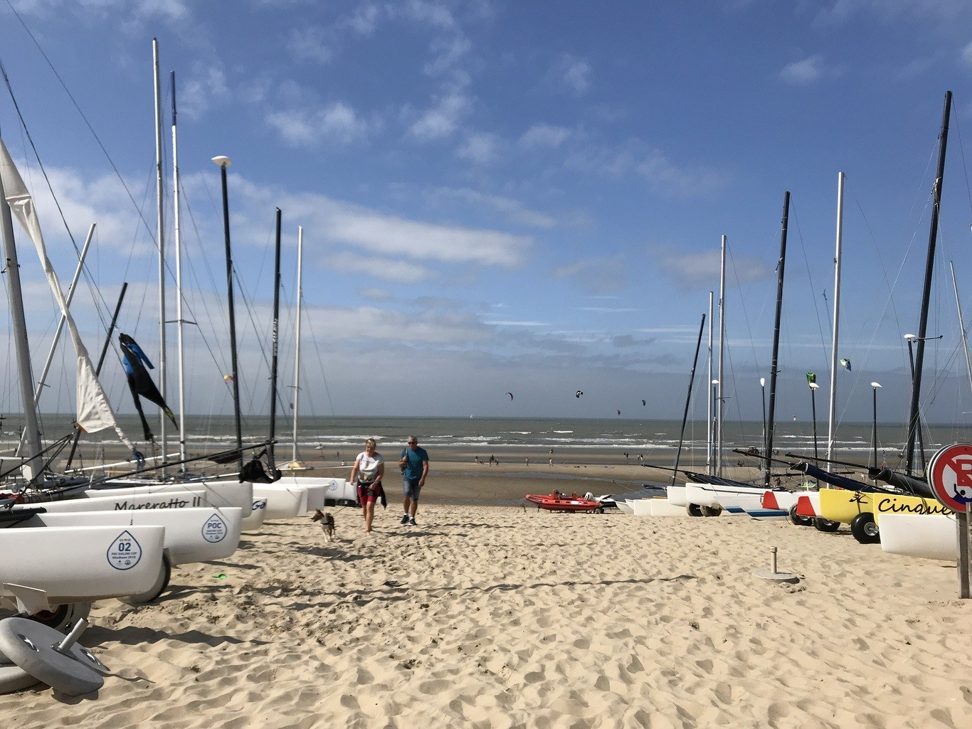 Boats line a sandy shore at the beach club in De Haan